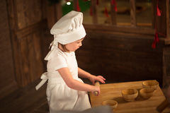 Girl cook with a rolling pin to stretch dough, the concept of ch Stock Photography