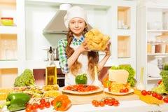 Girl in cook's uniform making Italian pasta Stock Image
