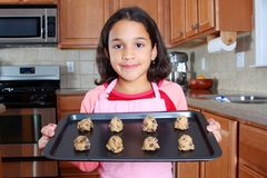 Girl With Cookies. Girl baking chocolate chip cookies in the kitchen stock photography