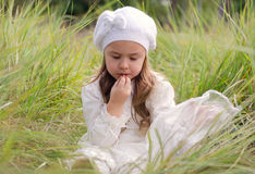 Girl with cookies. Little girl eating cookies on the grass in a meadow stock photo