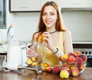 Girl cooking  beverages with electric blender from peaches Stock Images
