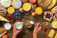 Girl cooking breakfast - granola with yogurt, fruits, berries, milk, yogurt, juice, cheese. Top view, copy space. Clean stock image