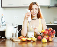 Girl cooking dairy beverages with electric blender Stock Image