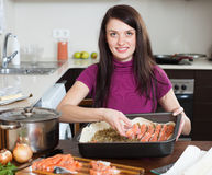 Girl cooking fish pie with salmon Stock Images