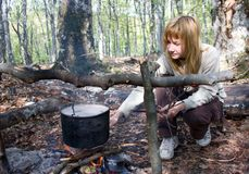 Girl cooking food on fire in camp Stock Photos