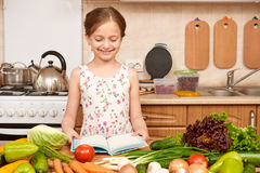 Girl cooking, kitchen interior with fresh fruits and vegetables on the table, healthy food concept Stock Images