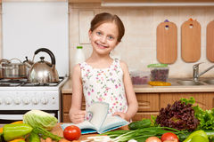 Girl cooking, kitchen interior with fresh fruits and vegetables on the table, healthy food concept Stock Photography