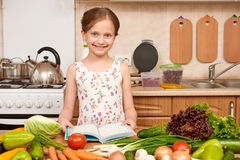 Girl cooking, kitchen interior with fresh fruits and vegetables on the table, healthy food concept Stock Photo