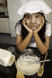 Girl with cooking mess. Girl in chef's hat in kitchen with a mess Royalty Free Stock Image
