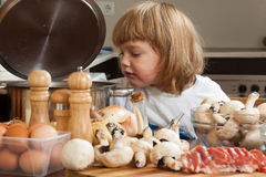 Girl cooking near kitchen table Royalty Free Stock Photos