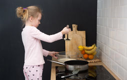 Girl cooking pancakes in kitchen Stock Photography