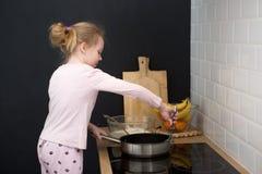 Girl cooking pancakes in kitchen Stock Photos