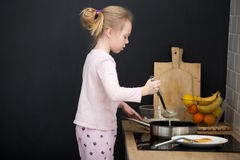 Girl cooking pancakes in kitchen Royalty Free Stock Photos