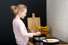 Girl cooking pancakes in kitchen Stock Images