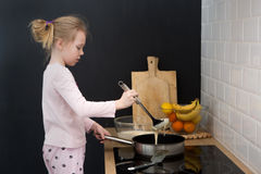 Girl cooking pancakes in kitchen Royalty Free Stock Photo