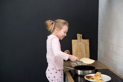 Girl cooking pancakes in kitchen Royalty Free Stock Photos