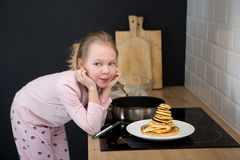 Girl cooking pancakes in kitchen Royalty Free Stock Photography