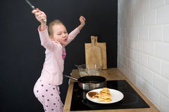 Girl cooking pancakes in kitchen Stock Photo