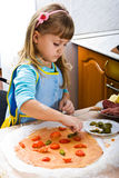 Girl cooking pizza. Little girl cooking pizza on the kitchen Royalty Free Stock Photos