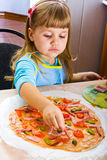 Girl cooking pizza. Little girl cooking pizza on the kitchen Royalty Free Stock Image