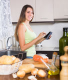 Girl cooking salmon fish and reading  ereader Royalty Free Stock Photo