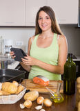 Girl cooking salmon fish and reading  ereader Stock Photography