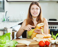 Girl cooking sandwiches with  baguette Stock Photography