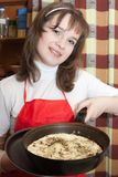 Girl cooking a scrambled eggs Stock Images