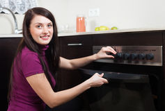 Girl cooking something in the oven Stock Photography