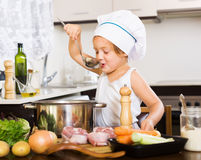 Girl cooking soup  with ladle Royalty Free Stock Photography