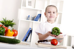 Girl cooking vegetables. Beautiful girl in the kitchen cooking vegetables Royalty Free Stock Images