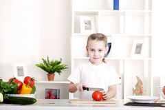 Girl cooking vegetables. Beautiful girl in the kitchen cooking vegetables Stock Images