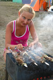 Girl cooks skewers Stock Image