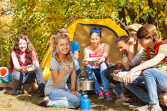 Girl cooks soup in the pot near yellow tent Stock Photography