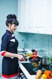 Girl cooks tomatoes for dinner. Stock Image