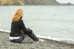 Girl in a cool day sitting on beach and looking thoughtfully into the distance Stock Images