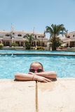 Girl cooling of in a pool Stock Photography