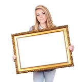 Girl with copy-space frame. Yong girl holding a golden frame with white copy-space, isolated on white background Royalty Free Stock Photography