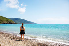 Girl on coral beach looking out to sea Stock Photography