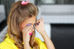 Girl corrects bright makeup. Tears in a cafe Stock Photography
