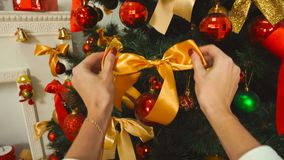 Girl corrects Orange bow on the Christmas tree. At home stock footage