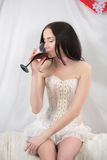 Girl in a corset. drinking red wine Stock Images