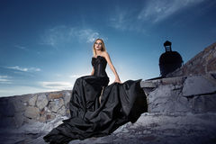 Girl in a corset with a long train at the wall. Stock Photography
