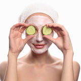 Girl with cosmetic cream. Funny young woman with a face pack.cucumber mask.girl with cosmetic cream on a cheek.Skin care concept Royalty Free Stock Images