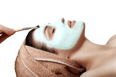 Girl with a cosmetic mask on her face, green clay, wrinkle treat. Beautiful girl with a green cosmetic mask on her face, brushing, clay, wrinkle, moisturizing Royalty Free Stock Photography
