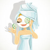 Girl in a cosmetic mask pack puts cucumbers on eye Royalty Free Stock Images