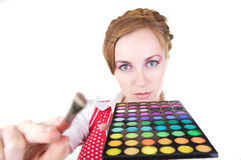 Girl with cosmetics. Young beautiful girl with cosmetics brush and color shadows Stock Photos