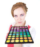 Girl with cosmetics. Young beautiful girl with cosmetics brush and color shadows Royalty Free Stock Image