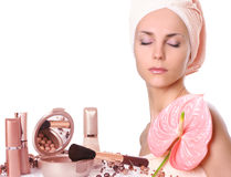 Girl with cosmetics. Young girl with pink flower Royalty Free Stock Images