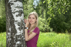 Girl costs at a birch in the afternoon Royalty Free Stock Image